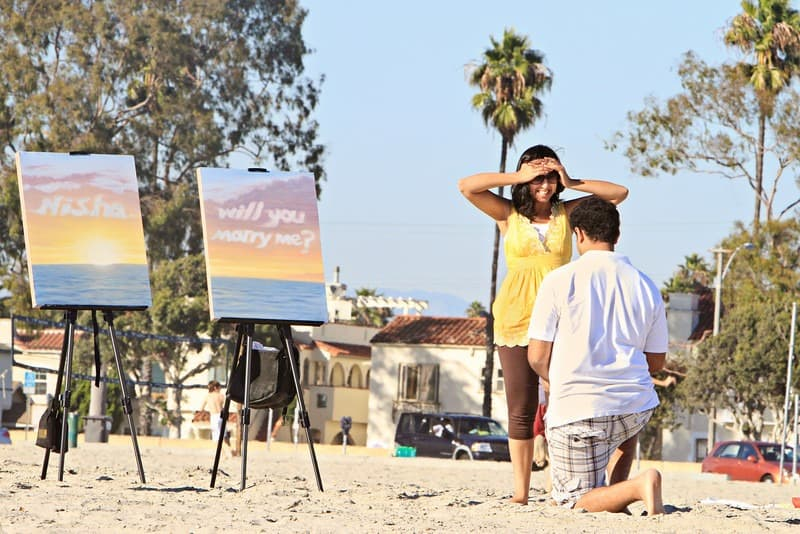 Beach engagement idea with paintings